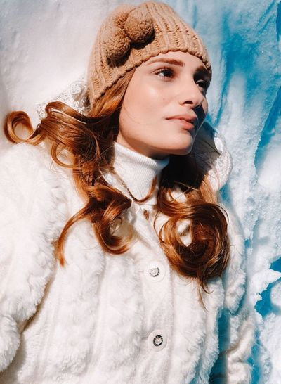 Portrait of young woman lying down in snow