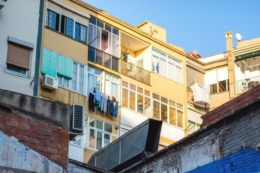 Architecture Building Exterior City Sunlight Built Structure Beauty Outdoors Multi Colored Sky No People Day Poble-sec Barcelona Portrait Of A City Windows, Doors Into The Soul Of The City SPAIN Clothesline Balcony Lifestyles Travel Destinations Blue Sky Layers City Life
