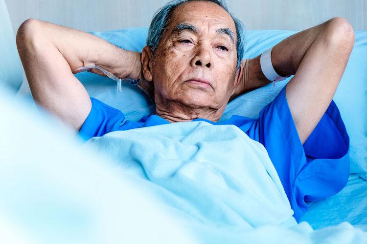 Senior Man Lying On Bed In Hospital
