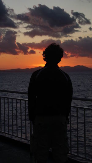 Silhouette of man standing by railing against sky during sunset