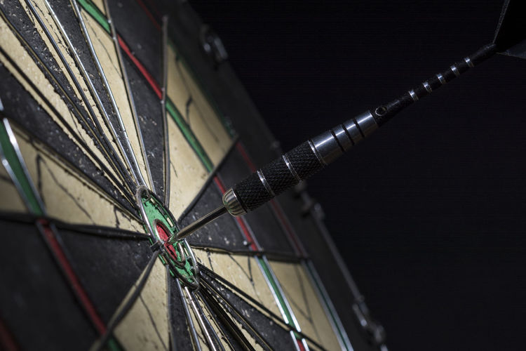 Dart in bulls eye of dartboard, close up Achieve Achievement Aspirations Business Target Accuracy Aim Backgrounds Black Background Bulls Eye Competition Concept Copy Space Dart Dartboard Focus Fortune Perfection Performance Precise Skill  Sports Target Strategy Success Winner