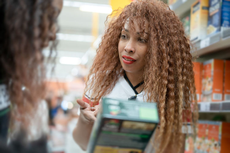 an attractive afro american woman talking at the supermarket with a package in her hand Hair Hairstyle Women Curly Hair Portrait Holding Indoors  Adult Real People Beautiful Woman Afro American Afro American Woman Shopping Mall Shopping Mall Talking Lifestyles Looking At Camera Packaging Store Looking Black Woman