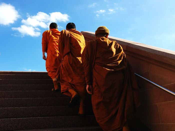 Rear view of monks walking on steps against sky