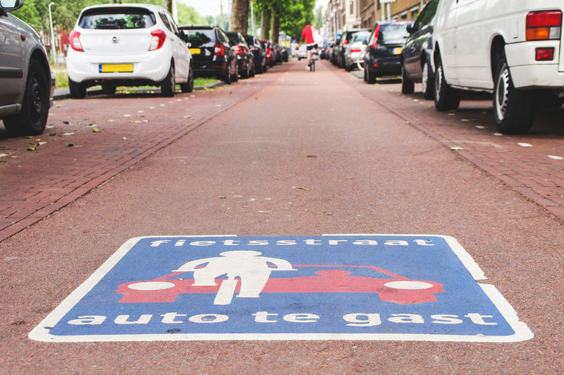Transportation City Sign Land Vehicle Mode Of Transportation Street Road Text Communication Direction Symbol Day Western Script Information Guidance Bicycle Lane Environmental Issues Modern Transportation City Street Netherlands The Hague Auto Te Gast Cars Are Guests Bicycle Priority