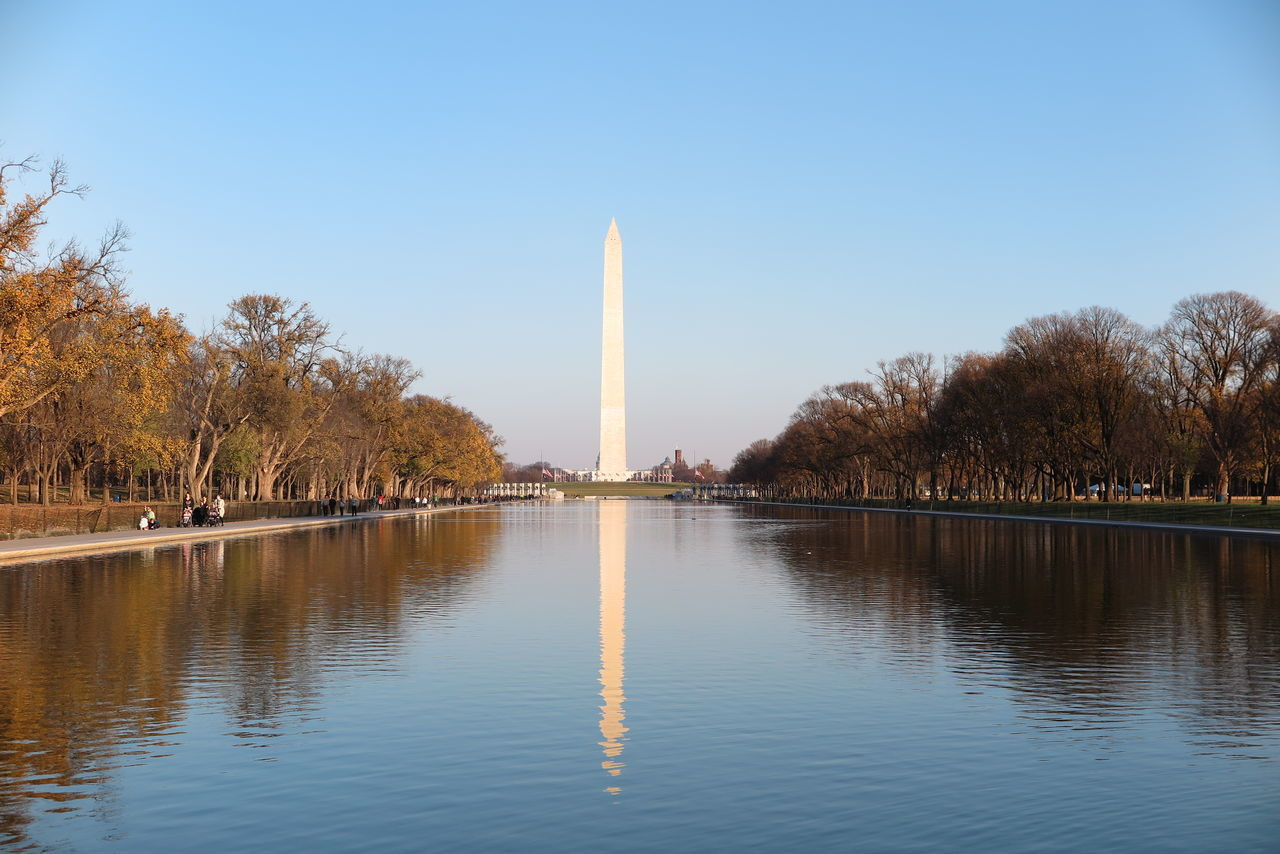 Washington Monument In Front Of Pond Against Sky