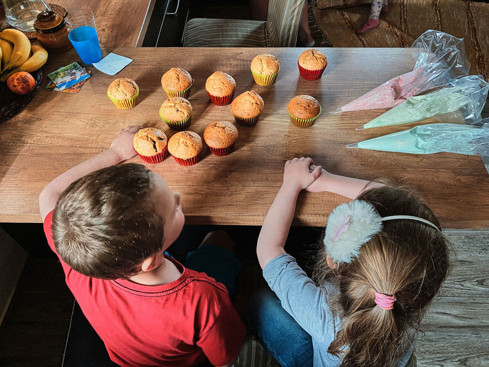 High angle view of kids sitting by table at home with cupcakes