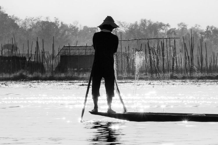 Rear view of man rowing boat in lake