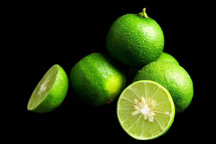 Close-up of green fruits against black background