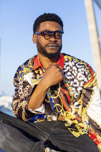 Close up portrait of young black bearded man wearing sunglasses sitting while looking camera in cool attitude in a sunny day Glasses Eyeglasses  Front View One Person Beard Portrait Looking At Camera Real People Casual Clothing Men Leisure Activity Mid Adult Lifestyles Sunglasses Smiling Facial Hair Males  Adult Sitting Fashion Outdoors Mature Men African American Black Man Sitting