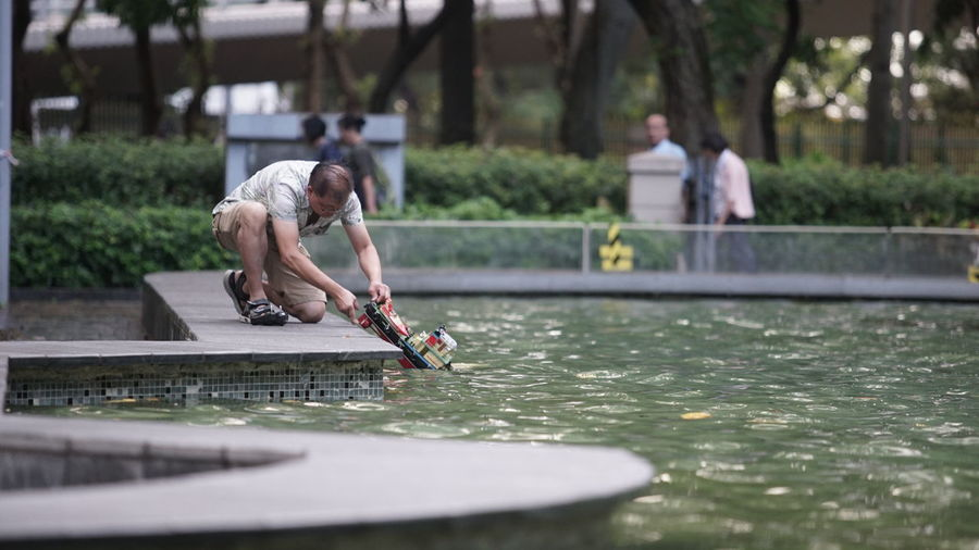 Man putting toy boat on swimming pool
