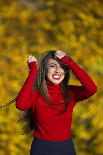 Pure Happiness Holiday Moments Happiness One Person Emotion Smiling Young Adult Cheerful Autumn Front View Hair Long Hair Clothing Adult Women Hairstyle Portrait Leisure Activity Three Quarter Length Waist Up Standing Young Women Human Arm Arms Raised Positive Emotion Outdoors Moments Of Happiness