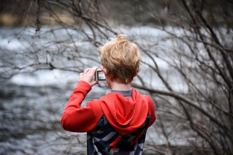 Rear View Of Boy Photographing Lake Through Digital Camera