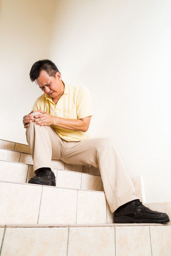 Asian middle age man with painful knee on steps and stairs Asian  Gout Paint the Town Yellow Adult Ageing Full Length Help Home Interior Indoors  Infection Inflammation Inflammed Knee Malaysian Males  Men Middle Ages One Person Sitting Steps And Staircases Suffering Tired