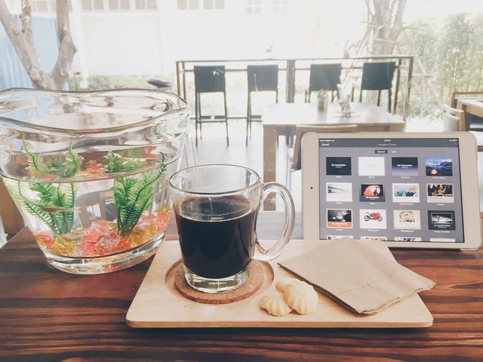 Close-up of black coffee and digital tablet