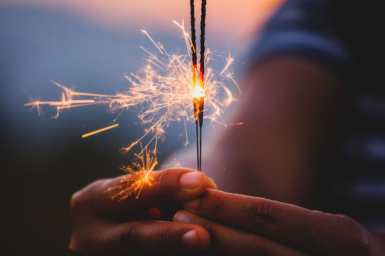 Cropped hand holding lit sparkler during sunset