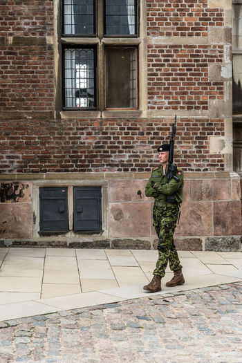Soldier guarding Rosemborg Castle in Copenhagen Adult Adults Only Architecture Armed Forces Army Army Soldier Brick Wall Building Exterior Built Structure Camouflage Clothing Day Full Length Holding Military Military Uniform One Person Outdoors Real People Standing Terrorism Uniform Weapon Window Young Adult Young Women