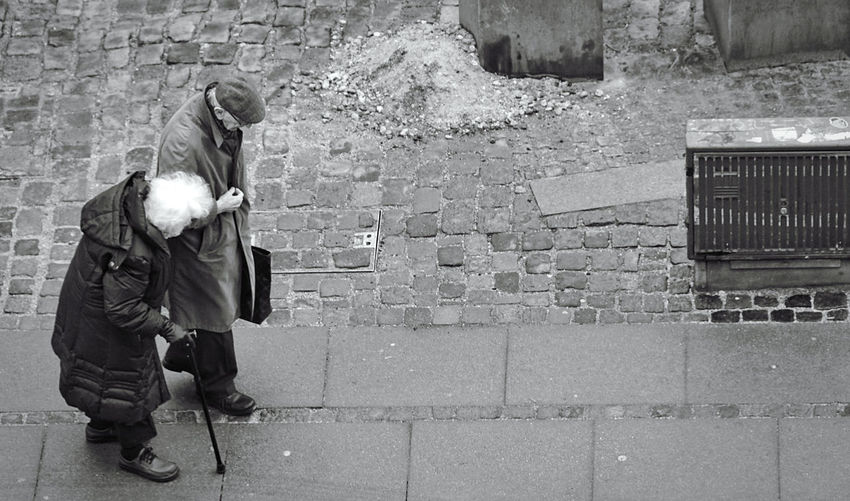 Side view of man holding woman walking on footpath