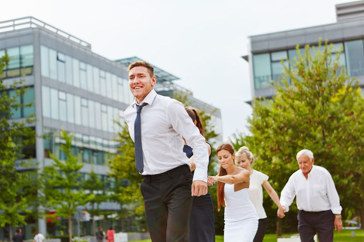 Business People Holding Hands While Walking Against Trees