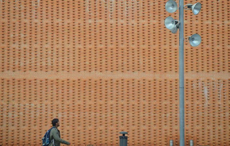 Man walking towards megaphones by brown wall