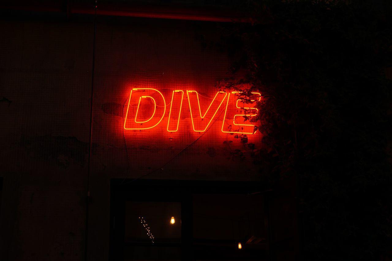Close-up of illuminated dive text at night