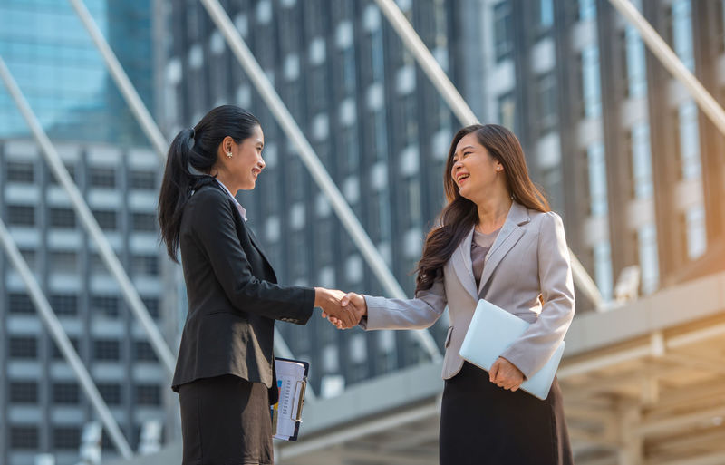 Business women working together. Built Structure Business Business Person Businessman Businesswoman City Communication Cooperation Corporate Business Day Downtown District Focus On Foreground Friendship Handshake Men Outdoors Smiling Teamwork Technology Togetherness Two People Well-dressed Women Young Adult Young Women