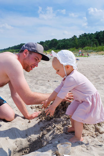 Child Childhood Beach Land Real People Innocence Leisure Activity Day Nature Outdoors Sand Dune Playing In Sand Sand Ocean Playing Father Father And Daughter Dad And Daughter Playtime Summer Time  Exploring