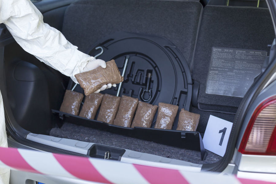 Drug smuggling. Drug bundles smuggled in a car trunk. Arrest Car Close-up Drug Hand Made Human Body Part Human Hand Illegal Indoors  Low Section Marijuana Narcotics One Person Packets People Police Smuggling Substance Trafficking Trunk Vehicle