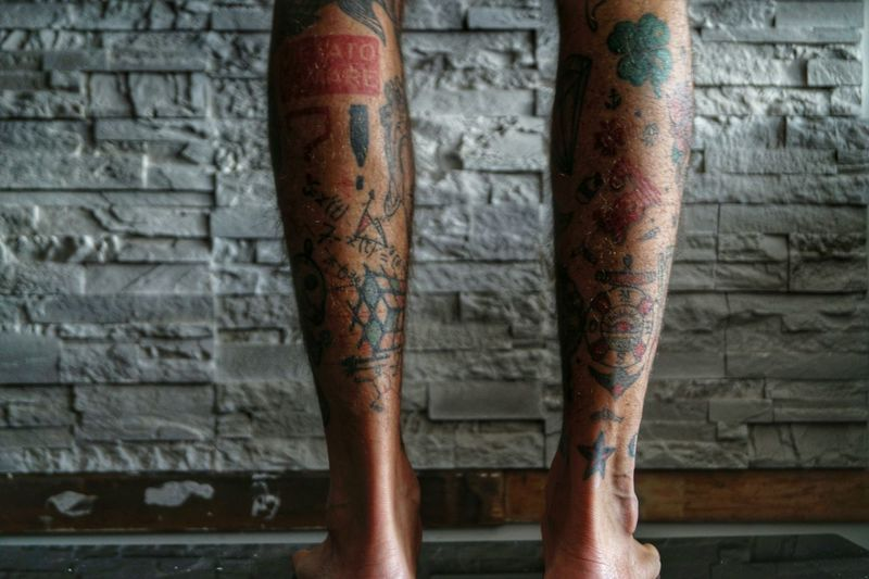 Low Section Of Man With Tattoo Against Brick Wall