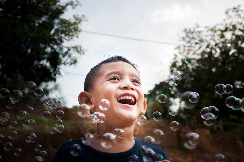 Close-up of cheerful boy with bubbles against sky