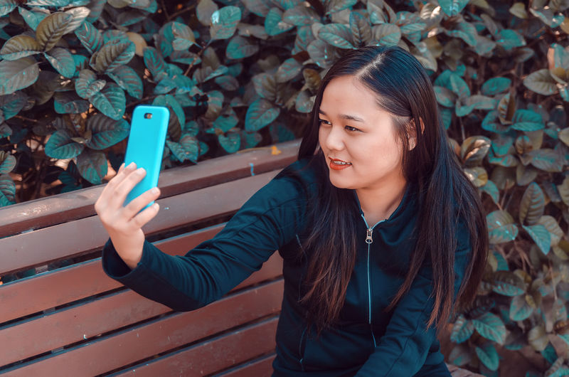 Young woman taking selfie on bench by plants