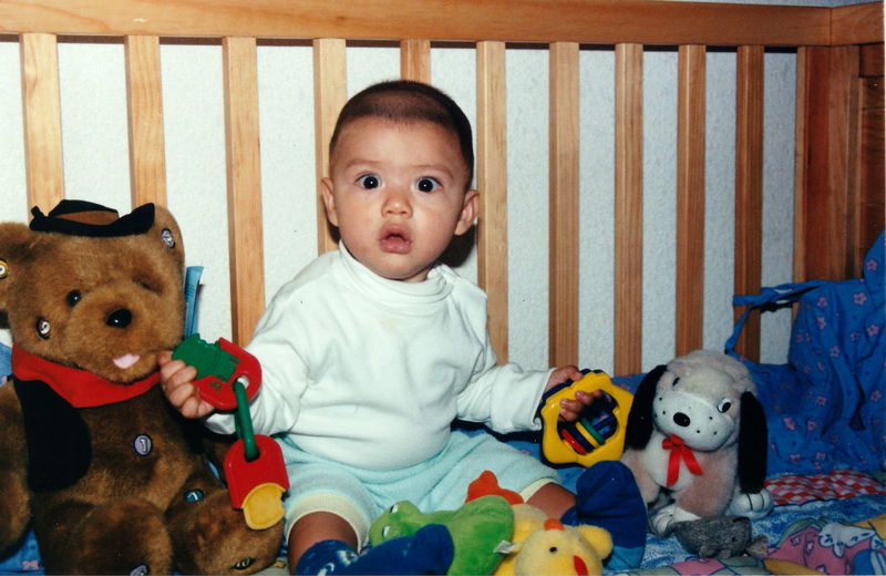 Portrait of cute baby boy sitting with toys in crib