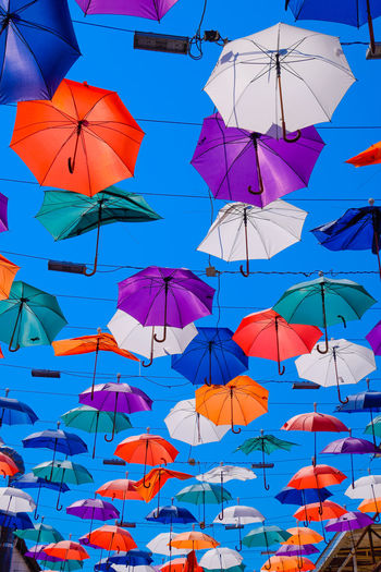 Low angle view of umbrellas hanging against blue sky