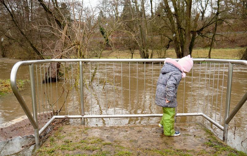 Full length of girl standing by railing against bare trees during winter