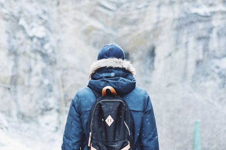 Rear view of person with backpack during snowfall