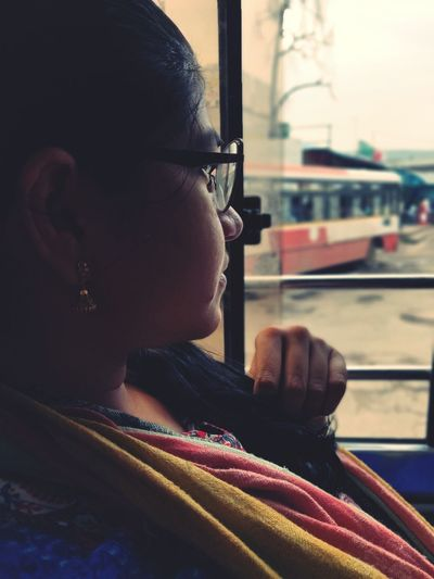 Side view of young woman sitting in bus