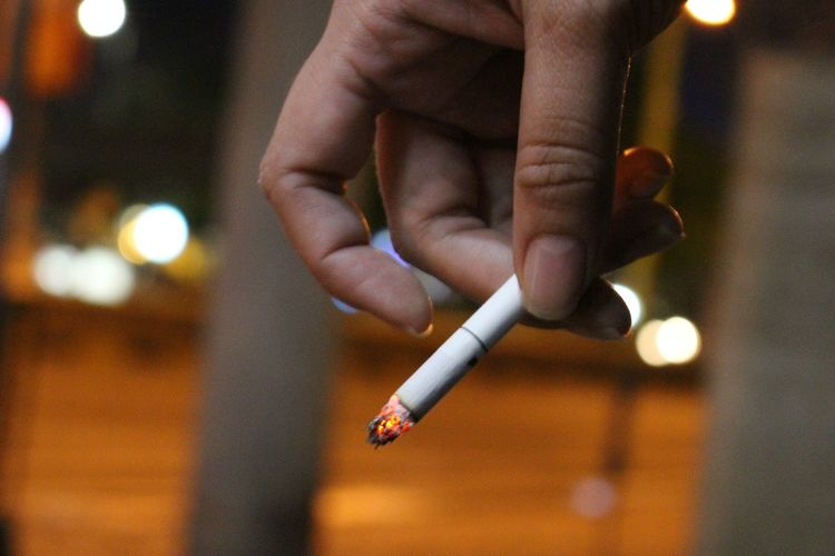 Close-Up Of Hand Holding Cigarette At Night