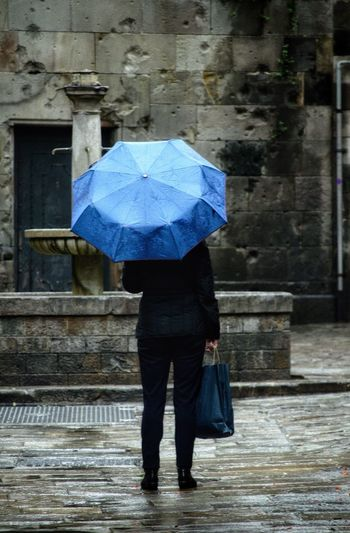 Rear view of woman walking with umbrella