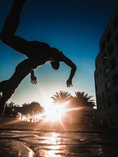 Silhouette man jumping in water against sky