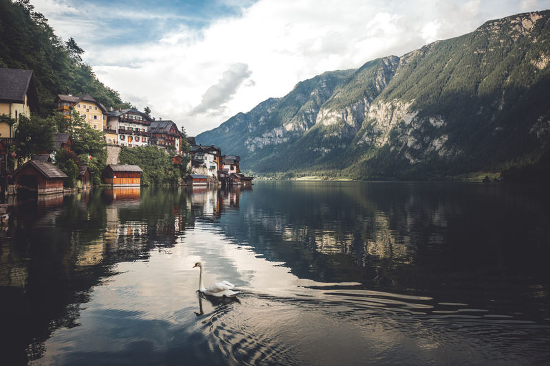 Lake by houses and mountains against sky