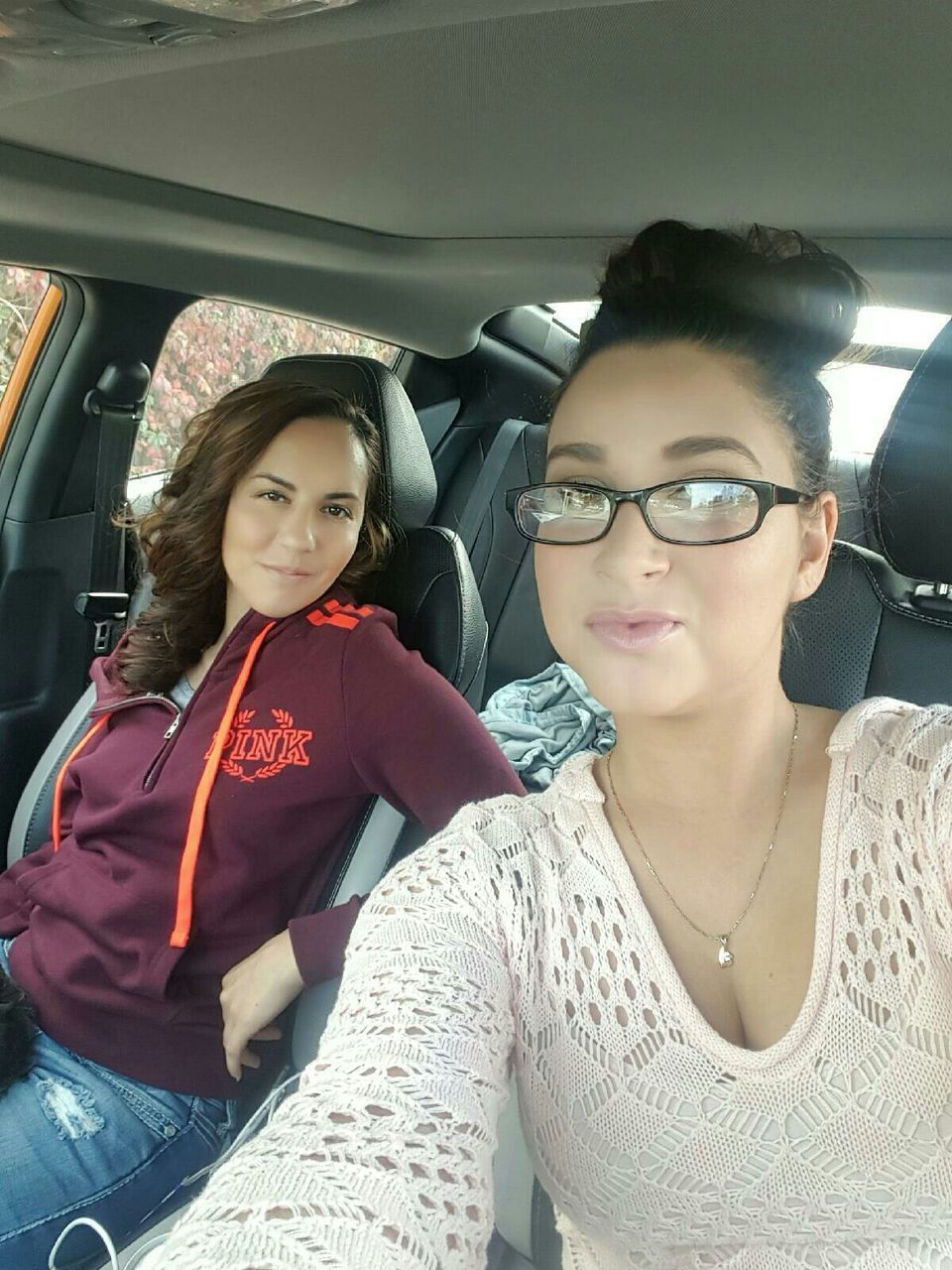 vehicle interior, transportation, young women, young adult, looking at camera, real people, sitting, lifestyles, eyeglasses, portrait, two people, casual clothing, smiling, mode of transport, front view, public transportation, travel, car interior, happiness, leisure activity, togetherness, day, vehicle seat, friendship