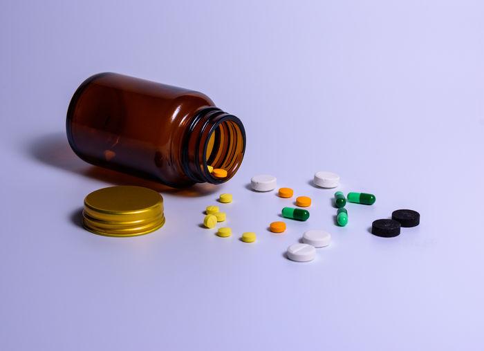 Close-up of medicines spilling from bottle on blue background