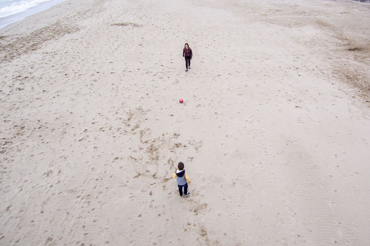 High angle view of woman playing soccer with son on sand at beach