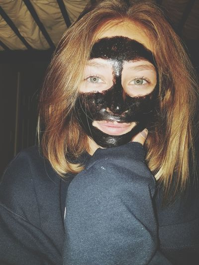 Portrait of teenage girl with black facial mask at home