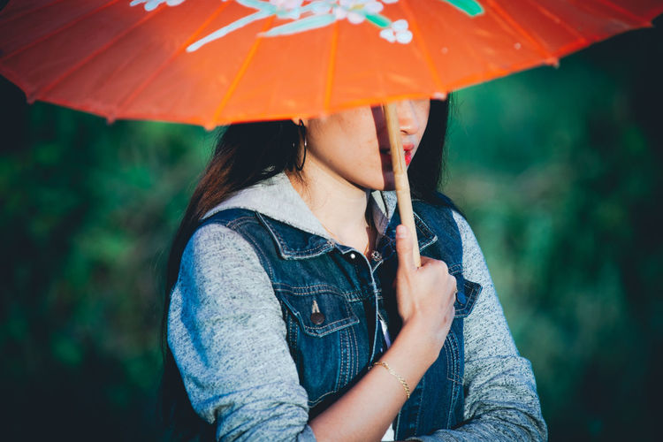Midsection of woman holding umbrella