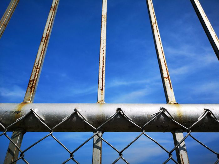 Low angle view of chainlink fence against blue sky