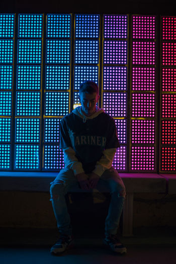 Full length of young man sitting against illuminated window