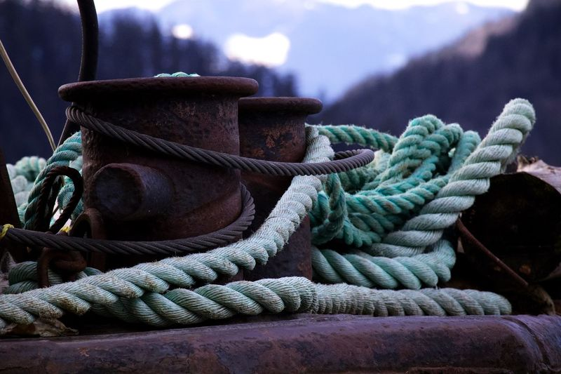 Close-up of rope tied on cleats at harbor