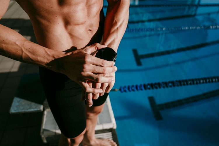 Midsection of shirtless man standing in swimming pool