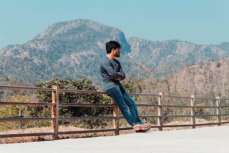 Full length of man siting on railing