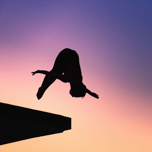 Low Angle View Of Silhouette Mid Adult Woman Jumping Against Clear Sky During Sunset